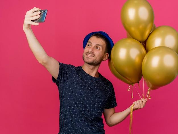 Sorridente bell'uomo caucasico che indossa il cappello blu del partito tiene palloncini di elio prendendo selfie guardando il telefono isolato su sfondo rosa con spazio di copia