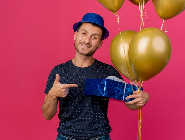 Smiling handsome caucasian man wearing blue party hat holds and points at helium balloons isolated on pink background with copy space