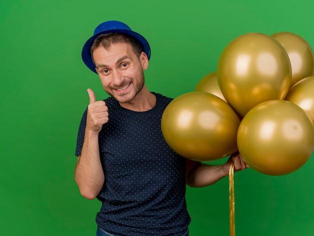 블루 파티 모자를 쓰고 웃는 잘 생긴 백인 남자 엄지 손가락 및 복사 공간 녹색 배경에 고립 된 헬륨 풍선을 보유