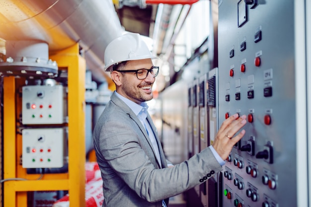Smiling handsome caucasian supervisor in gray suit and with helmet on head turning switch on. power plant interior.