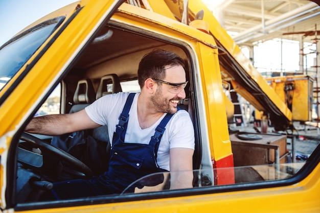 Усмехаясь красивый кавказский работник в общем входя в экскаватор и рассматривая плечо.