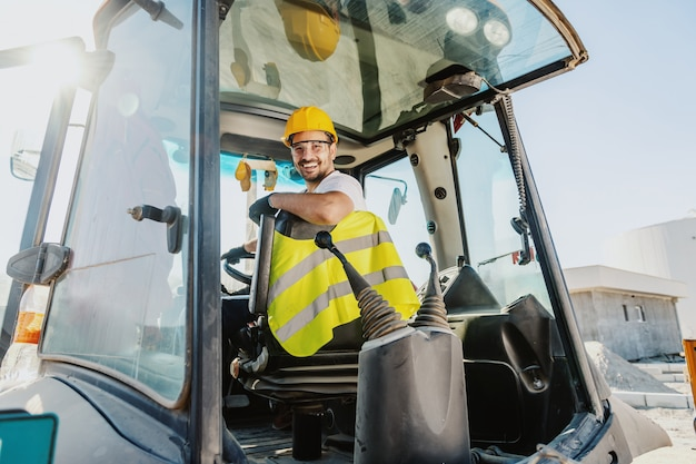 Smiling handsome caucasian worker in overall and with helmet on head driving excavator.