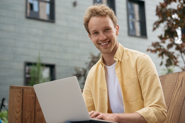 Smiling handsome computer programmer using laptop working online student studying outdoors