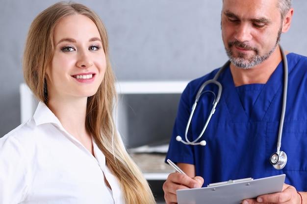 笑顔のハンサムな医者は、銀のペンを持ってパッドを見せている患者と通信します。