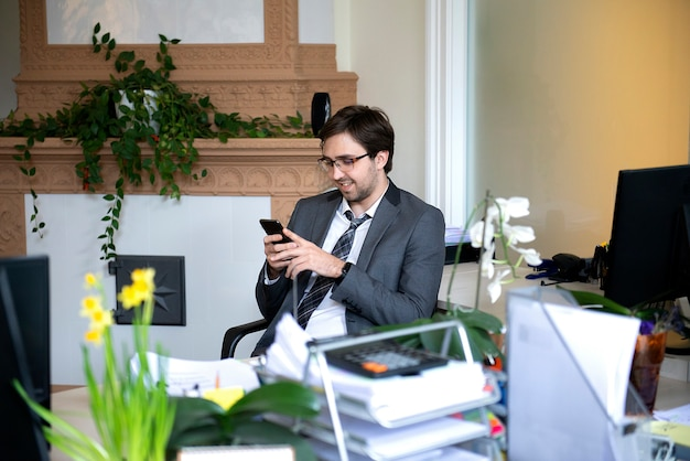 Улыбающийся красивый фрилансер, работающий удаленно из домашнего офиса. он говорит по телефону.