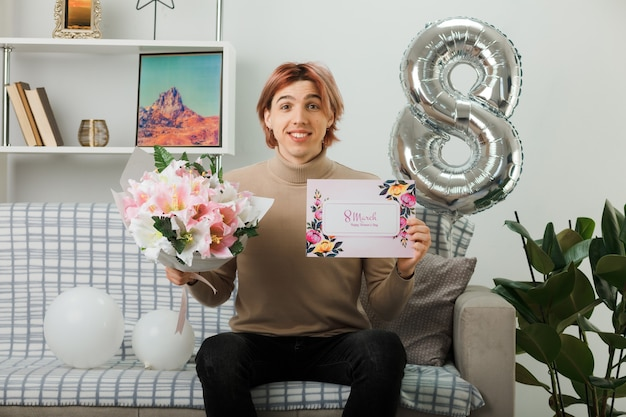 Smiling handsome guy on happy women day holding bouquet with greeting card sitting on sofa in living room