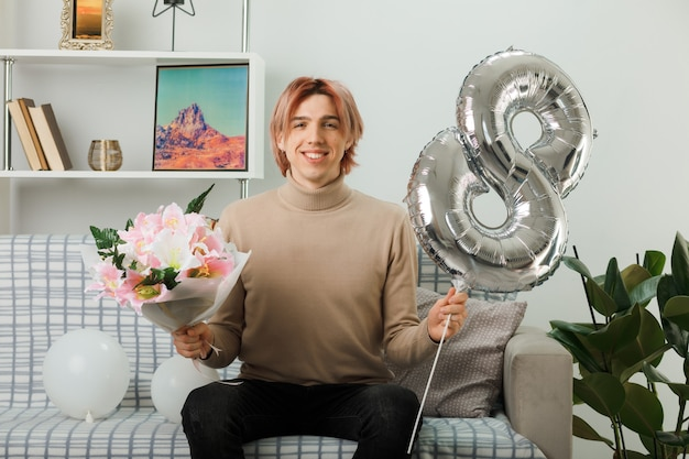 Smiling handsome guy on happy women day holding number eight balloon and bouquet sitting on sofa in living room
