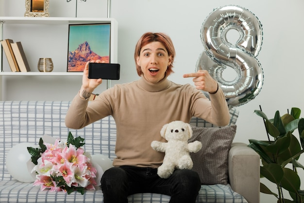 Sorridente bel ragazzo durante la giornata delle donne felici che tiene e indica l'orsacchiotto con il telefono seduto sul divano nel soggiorno