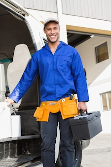 Smiling handsome handyman holding toolbox