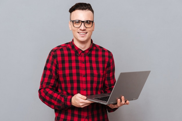 Улыбающийся красивый битник, держа в руках ноутбук