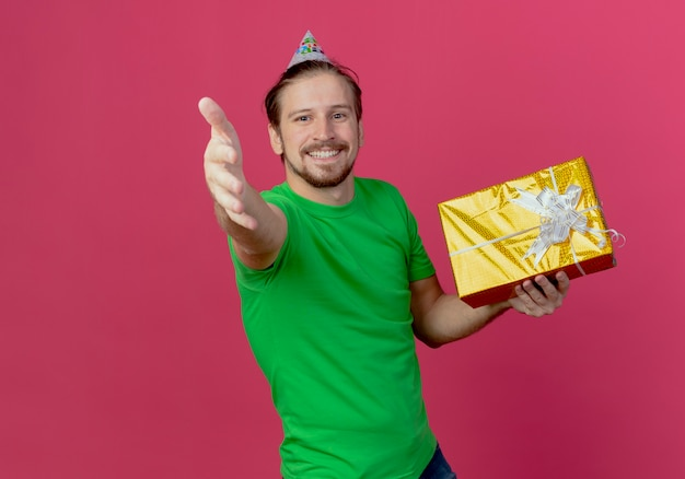 Smiling handsome man in birthday cap holds gift box and holds hand out isolated on pink wall