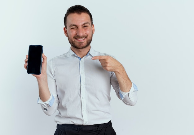 Smiling handsome man blinks eye holding and pointing at phone isolated on white wall