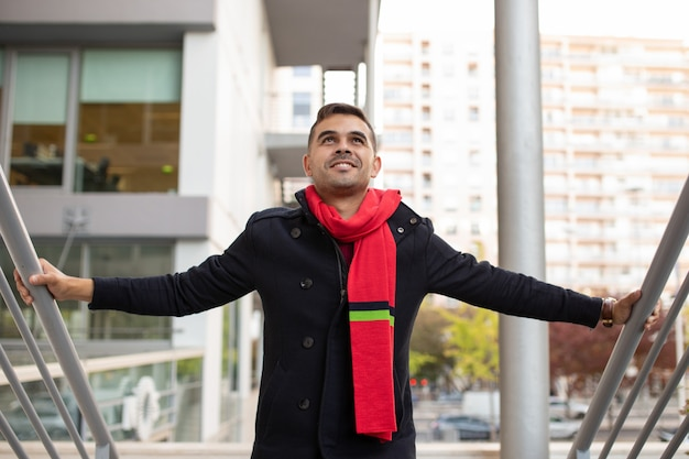 Smiling handsome man in coat and red scarf moving up stairs