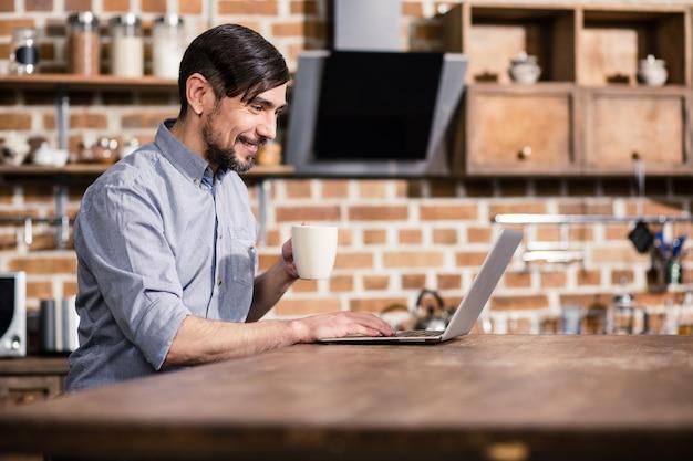 Улыбающийся красавец пьет кофе, используя свой ноутбук