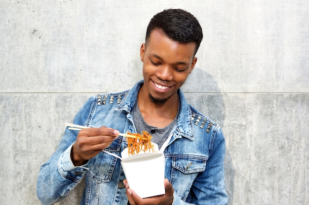 Smiling handsome man enjoying takeout noodles