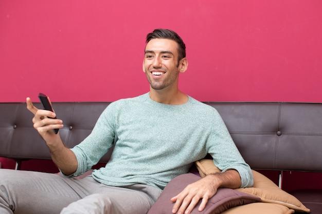 Улыбающийся красивый человек, наслаждаясь смотреть телевизор
