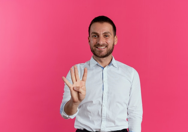 Smiling handsome man gestures four with hand isolated on pink wall