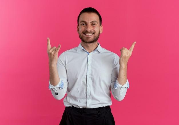 Улыбающийся красавец жесты рога знак рукой, изолированные на розовой стене