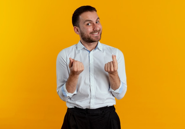 Smiling handsome man gestures money hand sign isolated on orange wall