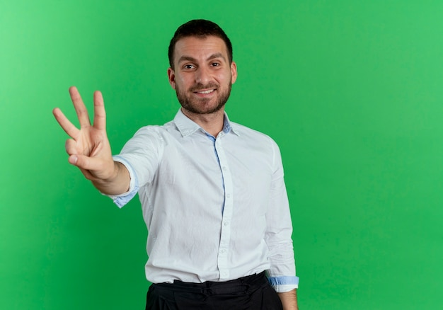 Smiling handsome man gestures three isolated on green wall