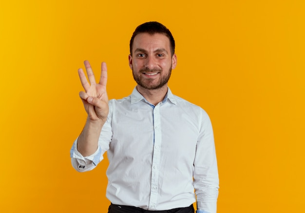 Smiling handsome man gestures three with fingers isolated on orange wall