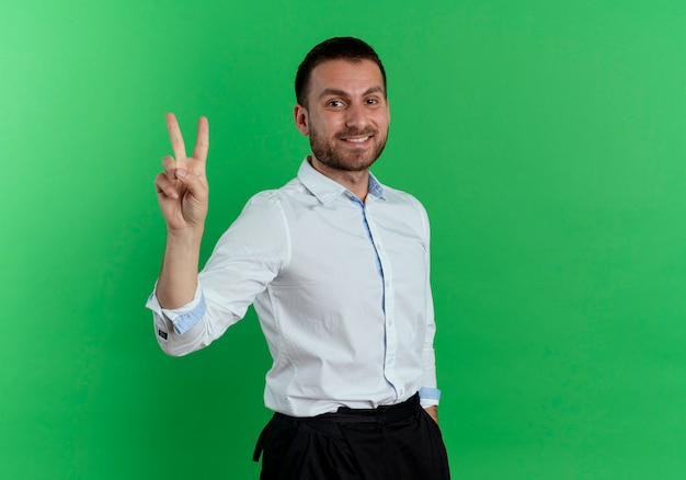 Smiling handsome man gestures victory hand sign isolated on green wall