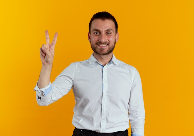 Sorridente uomo bello gesti il segno della mano di vittoria isolato sulla parete arancione