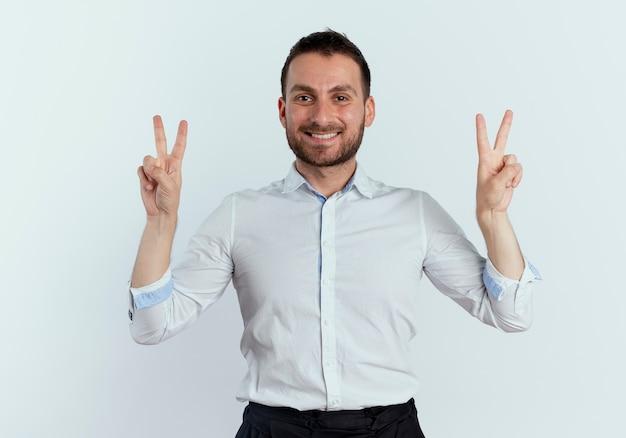 Sorridente uomo bello gesti il segno della mano di vittoria con due mani isolate sul muro bianco