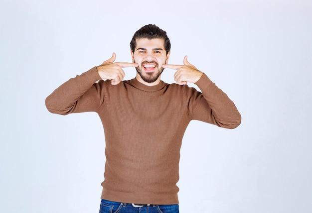 身振りで示すと彼の歯を指しているハンサムな男の笑顔。高品質の写真