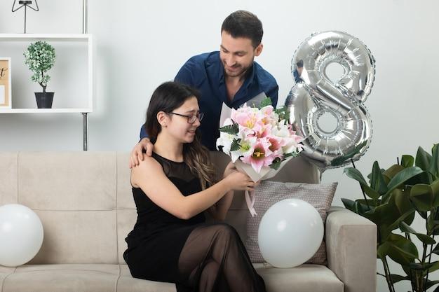 3월 국제 여성의 날에 거실 소파에 앉아 안경을 쓰고 흥분한 예쁜 젊은 여성에게 꽃다발을 주는 웃고 있는 잘생긴 남자