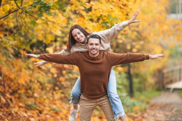 秋の公園で彼のガールフレンドに貯金箱を返すハンサムな男の笑顔