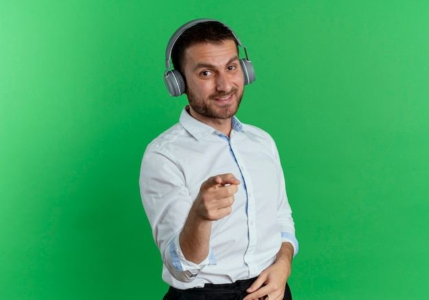 Smiling handsome man on headphones points isolated on green wall