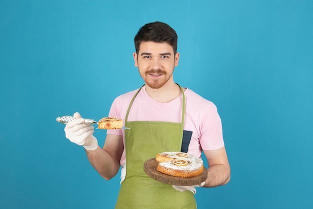 Sorridente bell'uomo che tiene fetta di torta e che guarda l'obbiettivo.