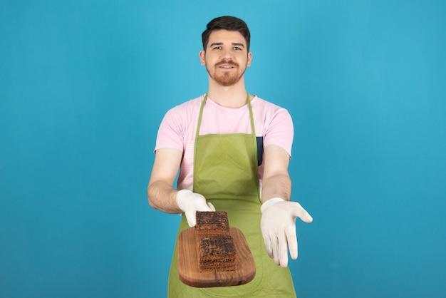 Sorridente bell'uomo che tiene le fette di torta sulla tavola di legno.