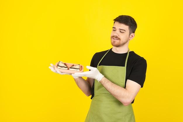 黄色に新鮮なケーキのスライスを保持しているハンサムな男の笑顔。