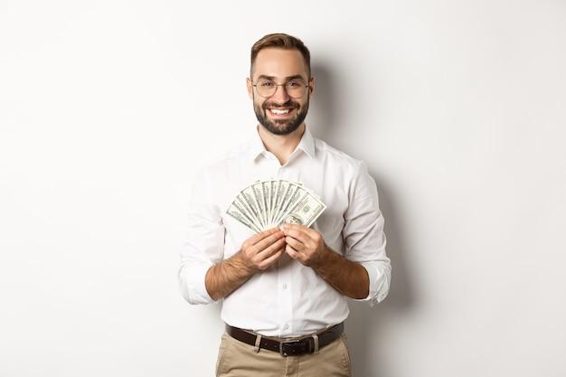 お金を持って、ドルを示して、白い背景の上に立っているハンサムな男の笑顔。コピースペース