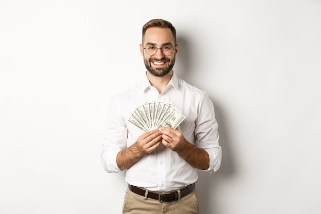 Smiling handsome man holding money, showing dollars, standing over white background. copy space
