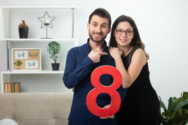 3월 국제 여성의 날에 빨간색 8자를 들고 거실에 서 있는 안경을 쓴 예쁜 젊은 여성을 가리키며 웃고 있는 잘생긴 남자