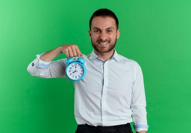 笑顔のハンサムな男は、緑の壁に孤立して見える目覚まし時計を保持します