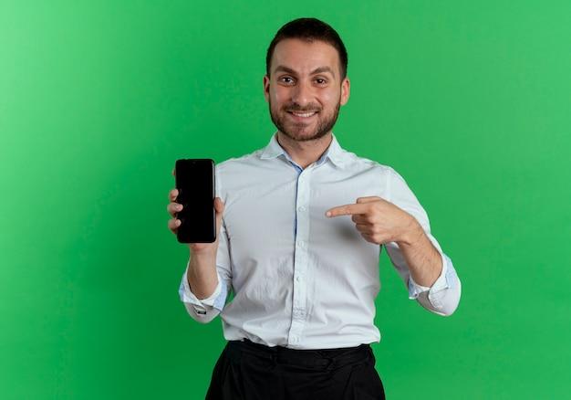 웃는 잘 생긴 남자 보유 및 녹색 벽에 고립 된 전화 포인트
