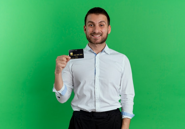 Smiling handsome man holds credit card isolated on green wall