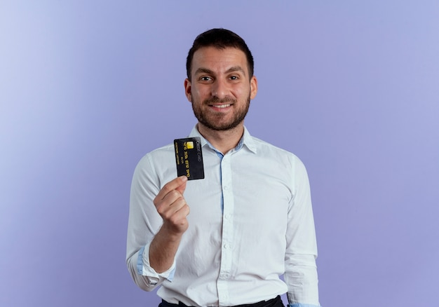 Smiling handsome man holds credit card isolated on purple wall