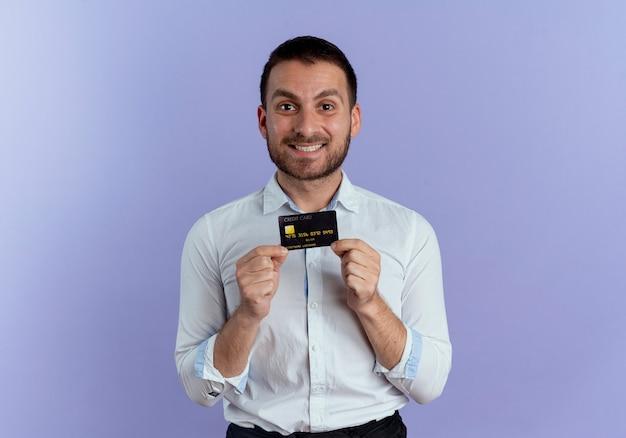 L'uomo bello sorridente tiene la carta di credito che sembra isolata sulla parete viola