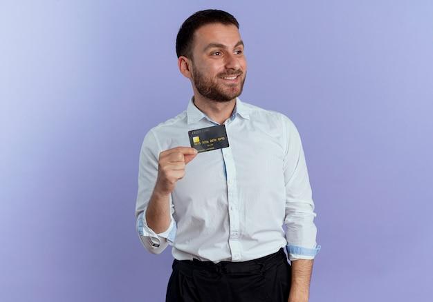 L'uomo bello sorridente tiene la carta di credito che esamina il lato isolato sulla parete viola