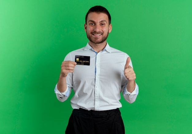 Smiling handsome man holds credit card and thumbs up isolated on green wall