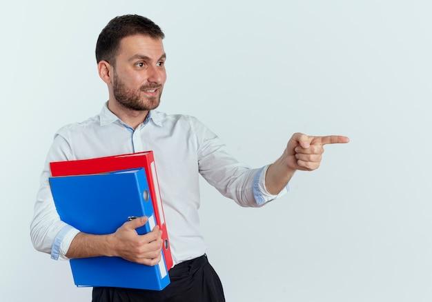 笑顔のハンサムな男は、白い壁に隔離された側を見て、指しているファイルフォルダを保持します