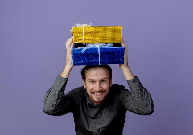 Улыбающийся красивый мужчина держит подарочные коробки над головой, глядя изолированно на фиолетовой стене