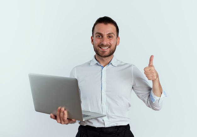 Smiling handsome man holds laptop thumbs up isolated on white wall