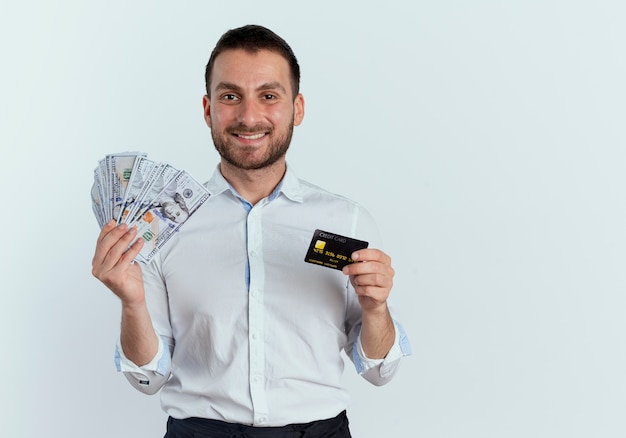 Smiling handsome man holds money and credit card isolated on white wall