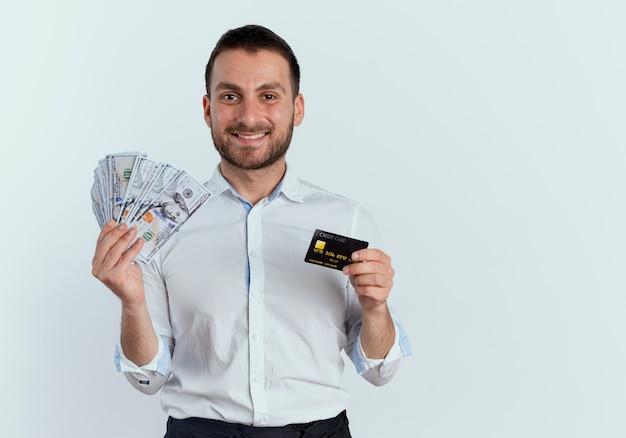 L'uomo bello sorridente tiene i soldi e la carta di credito isolata sulla parete bianca